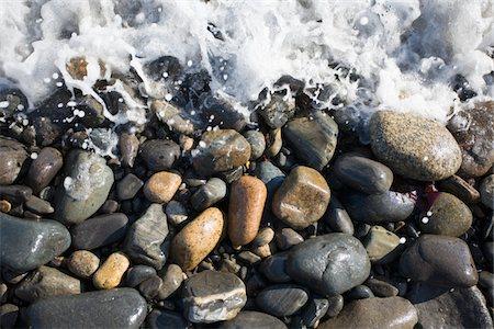 Surf splashes over stones on beach Stock Photo - Premium Royalty-Free, Code: 6106-05510771