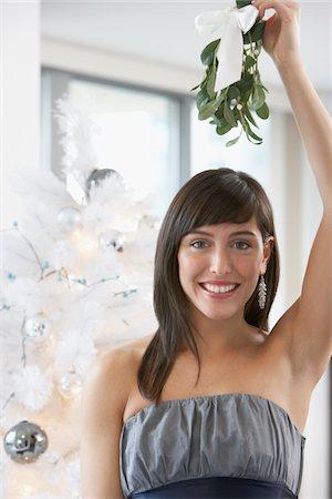 Portrait of woman holding mistletoe over her head Stock Photo - Premium Royalty-Free, Code: 6106-05511072