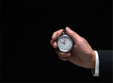 stop watch - Man holding stopwatch, close-up of hand Stock Photo - Premium Royalty-Free, Code: 6106-05511694