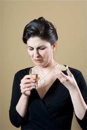 Woman grimacing at tequila shot Stock Photo - Premium Royalty-Free, Code: 6106-05512755