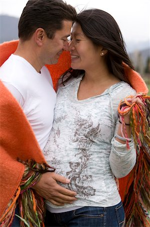 pregnant women kissing - Man and pregnant woman outdoors, hugging Stock Photo - Premium Royalty-Free, Code: 6106-05513354