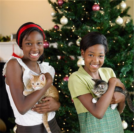 preteen girl pussy - Two sisters (11-13) holding kittens in front of Christmas tree Stock Photo - Premium Royalty-Free, Code: 6106-05525144