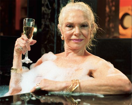 Mature woman relaxing in hot tub, holding champagne flute, portrait Stock Photo - Premium Royalty-Free, Code: 6106-05525740