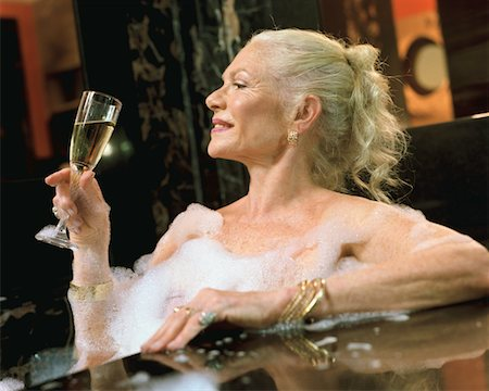 Mature woman relaxing in hot tub, holding champagne flute Stock Photo - Premium Royalty-Free, Code: 6106-05525741