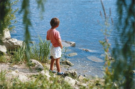 Boy (4-5) urinating by river, rear view Stock Photo - Premium Royalty-Free, Code: 6106-05529712