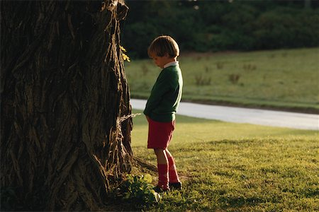 Boy (4-7) urinating on tree, side view Stock Photo - Premium Royalty-Free, Code: 6106-05529922