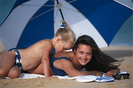 daughter kissing mother - Girl (4-5) kissing mother on back at beach Stock Photo - Premium Royalty-Free, Code: 6106-05531416