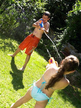 Brother and sister (9-12) having water fight in garden Stock Photo - Premium Royalty-Free, Code: 6106-05535315