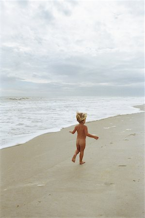Naked boy (2-4) running on beach, rear view Stock Photo - Premium Royalty-Free, Code: 6106-05537030