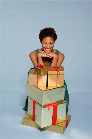 silver box - Young woman behind stack of gift boxes smiling, portrait Stock Photo - Premium Royalty-Free, Code: 6106-05537255