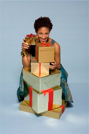 silver box - Young woman behind stack of gift boxes smiling, portrait Stock Photo - Premium Royalty-Free, Code: 6106-05537256
