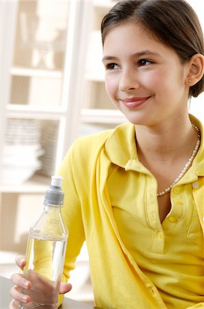 Girl (10-12) holding bottle of water, smiling Stock Photo - Premium Royalty-Free, Code: 6106-05539236