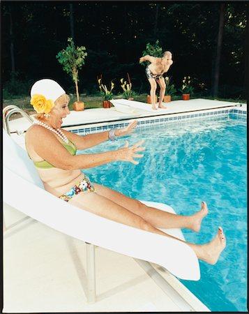seniors and swim cap - Eldely Woman on Pool Slide Stock Photo - Premium Royalty-Free, Code: 6106-05620487