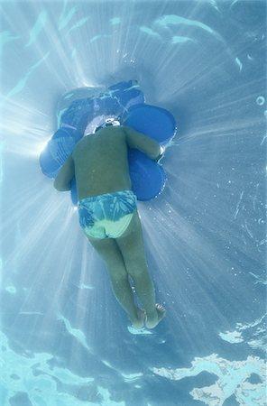 Underwater View of Child in Swimming Pool Stock Photo - Premium Royalty-Free, Code: 6106-05625024