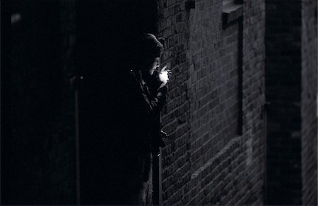 Teenage girl (15-17) lighting cigarette in alley (B&W) Stock Photo - Premium Royalty-Free, Code: 6106-05632994
