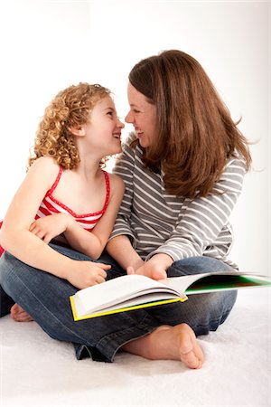Smiling mother and daughter with a book. Stock Photo - Premium Royalty-Free, Code: 6106-05759053