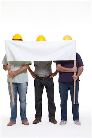 3 workers behind a banner Stock Photo - Premium Royalty-Free, Code: 6106-05787300