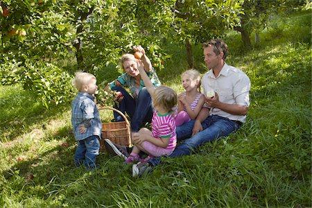 Family sitting in garden Stock Photo - Premium Royalty-Free, Code: 6106-05787758