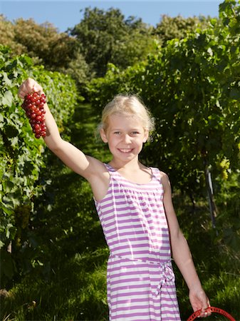 Portrait of girl showing grapes in vinyard Stock Photo - Premium Royalty-Free, Code: 6106-05787771