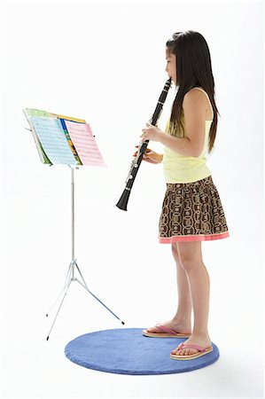 Girl (9-11) playing clarinet, looking at sheet music, side view Stock Photo - Premium Royalty-Free, Code: 6106-05843290