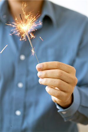 sparks with white background - Man holding sparkler Stock Photo - Premium Royalty-Free, Code: 6106-05843297