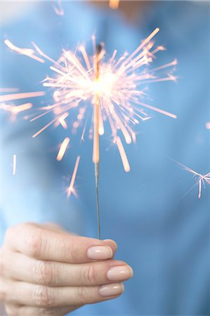 sparks with white background - Woman holding fire cracker, close-up Stock Photo - Premium Royalty-Free, Code: 6106-05843219