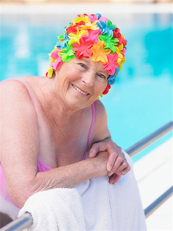 seniors woman in swimsuit - Senior woman wearing swimming hat standing by pool, smiling, portrait Stock Photo - Premium Royalty-Free, Code: 6106-05843388
