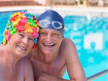 seniors and swim cap - Senior couple wearing swimming hats by pool, smiling, portrait Stock Photo - Premium Royalty-Free, Code: 6106-05843390