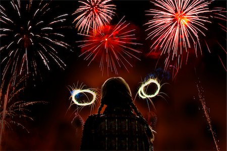 Girl waving sparklers watches firework display Stock Photo - Premium Royalty-Free, Code: 6106-05810475