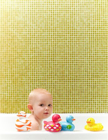 Toddler in bathtub playing with rubber duckies. Stock Photo - Premium Royalty-Free, Code: 6106-05810789