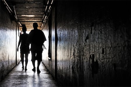 Silhouettes of couple walking in a dark corridor Stock Photo - Premium Royalty-Free, Code: 6106-05951490