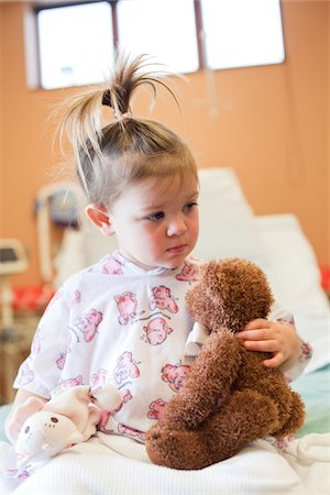 Toddler girl in hospital bed holding toy bear. Stock Photo - Premium Royalty-Free, Code: 6106-05951420