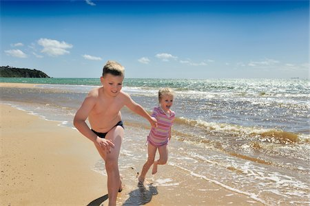 boy and girl running on beach Stock Photo - Premium Royalty-Free, Code: 6106-05952190
