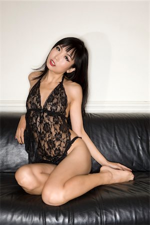 Woman in lingerie on sofa Stock Photo - Premium Royalty-Free, Code: 6106-05978484