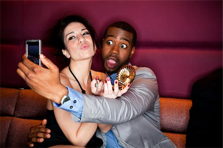 Two friends using a cell phone to take a picture. Stock Photo - Premium Royalty-Free, Code: 6106-06042703