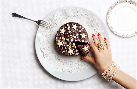 Luxurious hand picking out one slice of cake Stock Photo - Premium Royalty-Free, Code: 6106-06165495