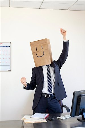 Businessmann wearing paper bag on head smiling Stock Photo - Premium Royalty-Free, Code: 6106-06165583