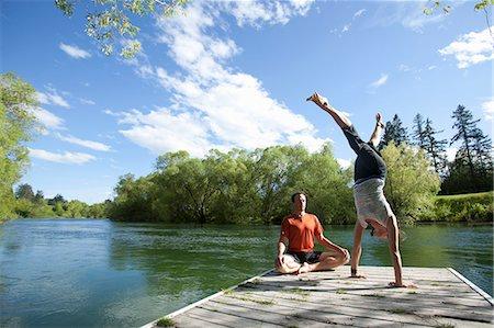 Couple practicing yoga and meditation on dock Stock Photo - Premium Royalty-Free, Code: 6106-06114117