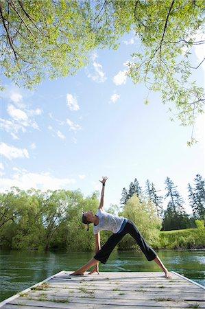Woman practicing yoga on dock Stock Photo - Premium Royalty-Free, Code: 6106-06114118