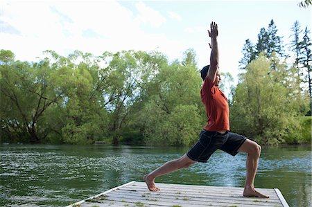 Man stretching on dock Stock Photo - Premium Royalty-Free, Code: 6106-06114119