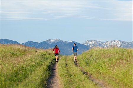 Young athletic couple jogging in mountains Stock Photo - Premium Royalty-Free, Code: 6106-06114379