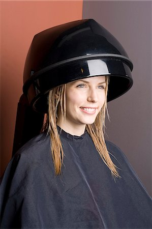 Smiling woman in a hood hair dryer Stock Photo - Premium Royalty-Free, Code: 6106-06114399