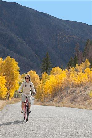 Woman riding on a cruiser bike Stock Photo - Premium Royalty-Free, Code: 6106-06114422