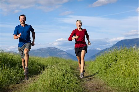 Couple running together on path in mountains Stock Photo - Premium Royalty-Free, Code: 6106-06114701