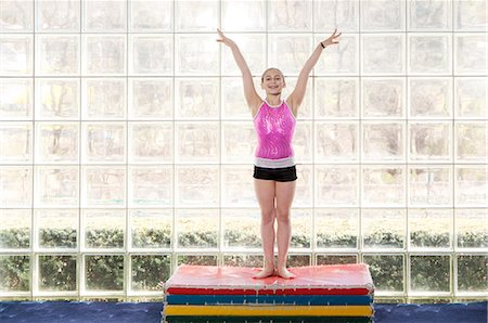 preteen girls gymnastics - young gymnast holding hands in air, smiling Stock Photo - Premium Royalty-Free, Code: 6106-06308082