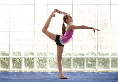 preteen girls gymnastics - young gymnast holding leg above head Stock Photo - Premium Royalty-Free, Code: 6106-06308086