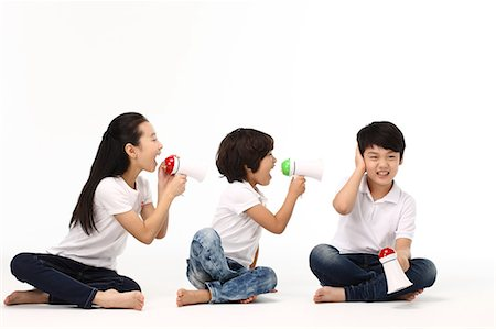 Children yelling into megaphone Stock Photo - Premium Royalty-Free, Code: 6106-06308767