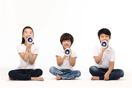 Children yelling into megaphone Stock Photo - Premium Royalty-Free, Code: 6106-06308768