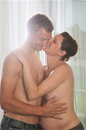 Pregnant woman and man embracing Stock Photo - Premium Royalty-Free, Code: 6106-06308931