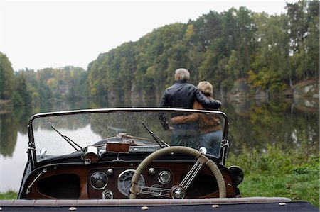 Senior couple looking at lake, in front of antique car Stock Photo - Premium Royalty-Free, Code: 6106-06309187